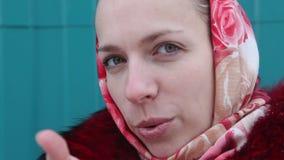 Het mooie meisje in een rode sjaal blaast een kus stock video