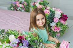 Het mooie meisje in een turkooise kleding zit en glimlacht dichtbij bloemen in een studio stock fotografie