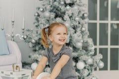 Het mooie meisje in een witte kleding zoals een prinses zit op een stuk speelgoed houten paard in een uitstekende studio, Nieuwja stock afbeelding