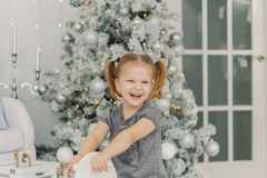 Het mooie meisje in een witte kleding zoals een prinses zit op een stuk speelgoed houten paard in een uitstekende studio, Nieuwja stock foto's