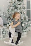 Het mooie meisje in een witte kleding zoals een prinses zit op een stuk speelgoed houten paard in een uitstekende studio, Nieuwja stock afbeeldingen