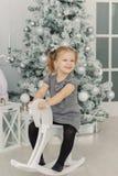 Het mooie meisje in een witte kleding zoals een prinses zit op een stuk speelgoed houten paard in een uitstekende studio, Nieuwja royalty-vrije stock foto's