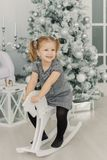 Het mooie meisje in een witte kleding zoals een prinses zit op een stuk speelgoed houten paard in een uitstekende studio, Nieuwja royalty-vrije stock afbeelding