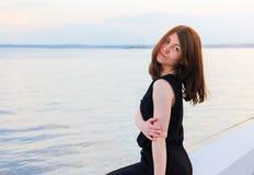 Het mooie meisje in een zwart kostuum bekijkt de camera op de achtergrond van de het plaatsen zon stock foto