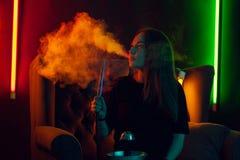 Het mooie meisje in een zwarte t-shirt rookt een waterpijp uitademend een rook bij een club van de luxenacht royalty-vrije stock foto