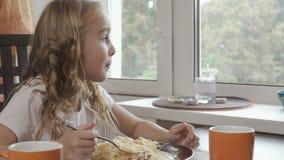Het mooie meisje eet haar diner in de keuken stock footage