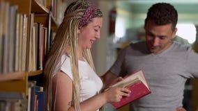 Het mooie meisje en een knappe kerel communiceren in een bibliotheek stock videobeelden
