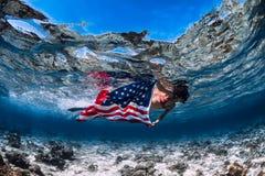 Het mooie meisje freediver zwemt over zandige overzeese bodem met de vlag van Verenigde Staten stock foto's