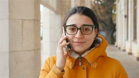 Het mooie meisje gaat en spreekt op de telefoon Langzaam motieclose-up stock videobeelden