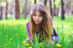 Het mooie meisje gaat zitten op het gras met bloemen Stock Fotografie