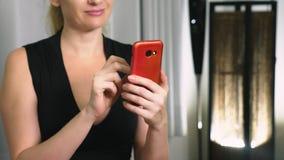 Het mooie meisje gebruikt een cellulaire smartphone terwijl het zitten in de woonkamer in de avond Gelukkige glimlachende jonge v stock video