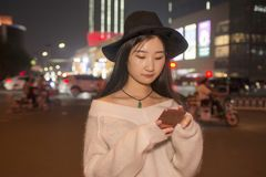 Het mooie meisje gebruikt een mobiele telefoon in de straten bij nacht Royalty-vrije Stock Foto