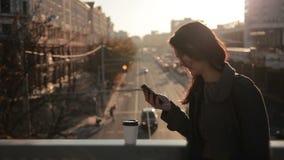 Het mooie meisje gebruikt een smartphone op een stadsbrug