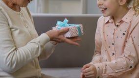 Het mooie meisje geeft heden aan oma, wenst gelukkige verjaardag, eerbied en liefde stock footage