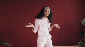 Het mooie meisje gekleed in roze pyjama's heeft pret dansend op het bed bij moderne flat Het gelukkige jonge vrouw onderzoeken stock footage