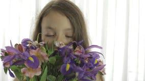 Het mooie meisje geniet van boeket van irissen en alstroemeria stock videobeelden