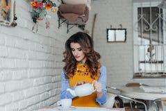Het mooie meisje giet thee in een koffie Royalty-vrije Stock Foto's