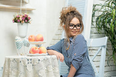Het mooie meisje in glazen zit bij een lijst met fruit in een heldere ruimte Stock Fotografie