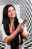 Het mooie meisje glimlacht en houdt mobiele telefoon Stock Foto's