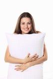 Het mooie meisje glimlacht en omhelst haar hoofdkussen Stock Foto