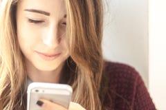 Het mooie meisje glimlacht en onderzoekt de telefoon Royalty-vrije Stock Afbeelding
