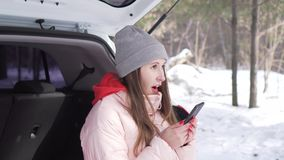 Het mooie meisje in grijze hoed en roze jasje kwam in de winterpark aan in haar witte auto stock footage