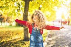 Het mooie meisje heeft pret in het park, de herfsttijd stock foto's