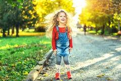 Het mooie meisje heeft pret in het park, de herfsttijd stock afbeelding