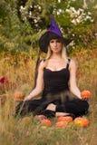 Het mooie meisje in heksenkostuum opleidingslotusbloem stelt Stock Foto