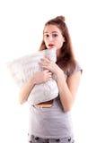Het mooie meisje in het hoofdkussen van de beddegoedgreep en maakt verrassingsgezicht Royalty-vrije Stock Afbeeldingen