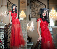 Het mooie meisje in het lange rode kleding stellen in een uitstekende scène. Jonge mooie vrouw die een rode kleding in luxelandsch Stock Fotografie