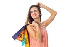 Het mooie meisje hief in hand vele gekleurde pakketten op en verheugt zich geïsoleerd op witte achtergrond Stock Afbeeldingen