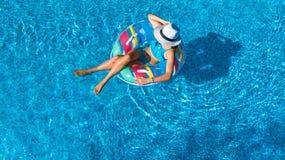 Het mooie meisje in hoed in zwembad lucht hoogste mening van hierboven, vrouw ontspant en zwemt op opblaasbare ringsdoughnut en h royalty-vrije stock foto