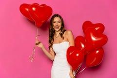 Het mooie meisje houdt ballons in twee handen op de dag van Valentine ` s stock afbeelding
