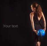 Het mooie meisje houdt blauwe voetbalbal op zwarte bac royalty-vrije stock fotografie