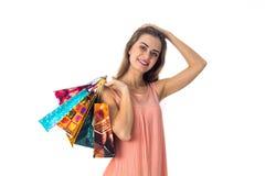 Het mooie meisje houdt de bal achter zijn hoofd en plotseling houdt de hand de gekleurde pakketten met giften op een wit geïsolee Royalty-vrije Stock Foto's
