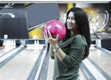 Het mooie meisje houdt een kegelenbal stock afbeeldingen