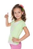 Het mooie meisje houdt haar duim tegen Royalty-vrije Stock Foto's