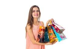 Het mooie meisje houdt vele pakketten en glimlachen in hand geïsoleerd op witte achtergrond Royalty-vrije Stock Fotografie
