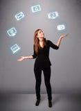 Het mooie meisje jongleren met met elecrtonic apparatenpictogrammen Royalty-vrije Stock Afbeeldingen