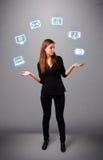 Het mooie meisje jongleren met met elecrtonic apparatenpictogrammen Royalty-vrije Stock Foto's