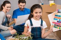 Het mooie meisje kiest een kleur van verf op kleurenpalet terwijl haar ouders reparaties doen royalty-vrije stock afbeeldingen