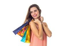 Het mooie meisje kijkt aan de kant en de holding verschillende die pakketten op witte achtergrond worden geïsoleerd Royalty-vrije Stock Afbeeldingen