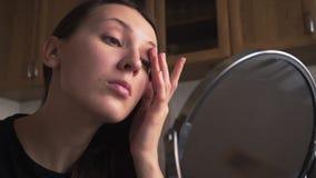 Het mooie meisje kijkt in een spiegel en past camouflagestift op de huid toe, omhoog doet een merk stock videobeelden