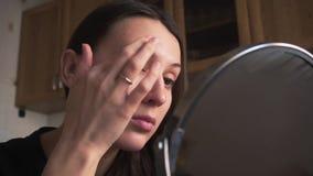 Het mooie meisje kijkt in een spiegel en en past camouflagestift toe, omhoog doet een merk stock videobeelden
