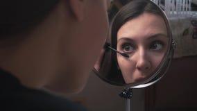 Het mooie meisje kijkt in een spiegel en schildert de wenkbrauwen met een potlood, omhoog doet een merk stock footage