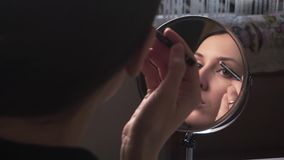 Het mooie meisje kijkt in een spiegel en schildert de wenkbrauwen met een potlood, omhoog doet een merk stock videobeelden