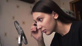 Het mooie meisje kijkt in een spiegel en schildert de wenkbrauwen met een potlood, omhoog doet een merk stock video