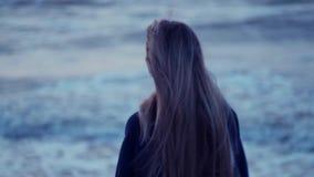 Het mooie meisje kijkt naar het overzees en de draaien aan camera, haar haar ontwikkelt zich, wind, golven tegen de achtergrond stock video