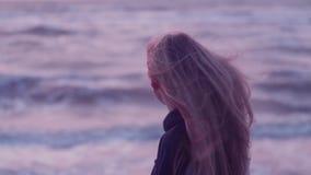 Het mooie meisje kijkt naar het overzees en draait camera, ontwikkelt haar haar zich, wind, golven tegen de achtergrond stock video